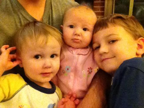 All three kids sitting on Daddy's lap. ❤