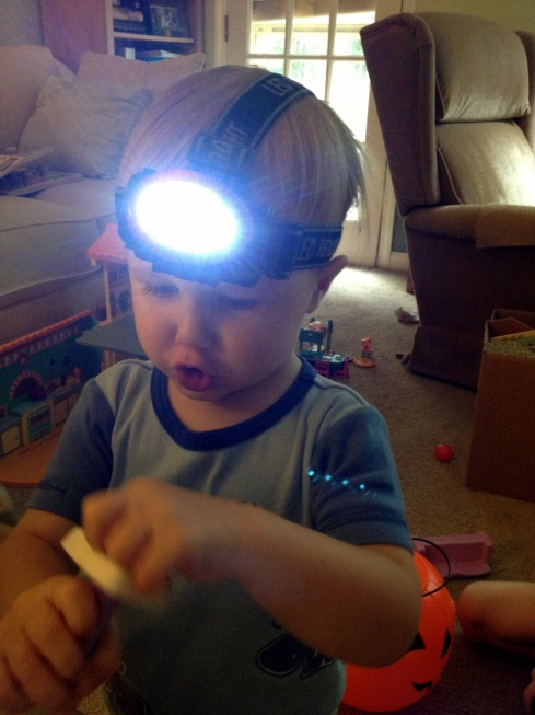 William wore his headlight while he worked on some toys